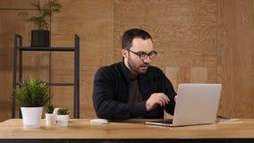 Homem novo que pensa ativamente na frente do portátil video estoque