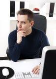 Homem novo que pensa na frente de seu computador Imagens de Stock Royalty Free