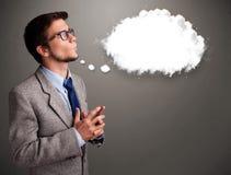 Homem novo que pensa sobre o discurso da nuvem ou a bolha do pensamento com bobina Fotografia de Stock Royalty Free