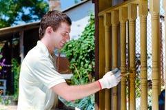 Homem novo que pinta a cerca de madeira Fotos de Stock