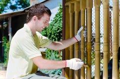 Homem novo que pinta a cerca de madeira no jardim Foto de Stock Royalty Free