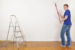 Homem novo que pinta uma parede Foto de Stock Royalty Free