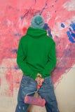 Homem novo que pinta uma parede Fotografia de Stock Royalty Free