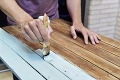 Homem novo que pinta uma tabela de madeira velha Imagem de Stock