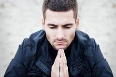Homem novo que praying Imagem de Stock