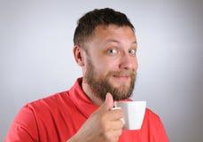 Homem novo que prende um copo de café Fotografia de Stock