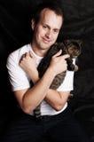 Homem novo que prende um gato Fotos de Stock