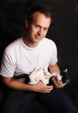 Homem novo que prende um gato preto e branco Fotografia de Stock