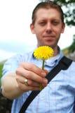 Homem novo que prende uma flor Imagens de Stock Royalty Free