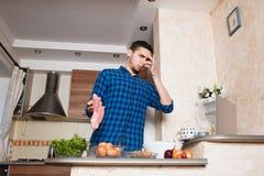 Homem novo que prepara a carne em sua cozinha, olhando no quadro Foto de Stock Royalty Free