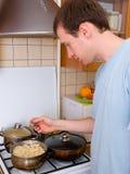 Homem novo que prepara o alimento Fotos de Stock Royalty Free