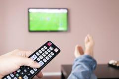 Homem novo que presta atenção à televisão, o cont remoto Imagens de Stock
