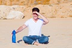 Homem novo que protege seus olhos no deserto Fotografia de Stock Royalty Free