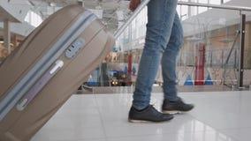 Homem novo que puxa a mala de viagem no terminal de aeroporto moderno O indivíduo de viagem que veste o estilo ocasional esperto  video estoque