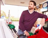 Homem novo que reabastece um carro em um posto de gasolina fotos de stock