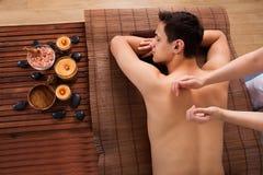 Homem novo que recebe a massagem traseira nos termas imagem de stock royalty free