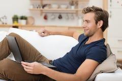 Homem novo que relaxa com um laptop Fotografia de Stock Royalty Free