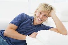 Homem novo que relaxa em casa Foto de Stock Royalty Free
