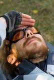 Homem novo que relaxa na grama que olha acima Fotos de Stock Royalty Free