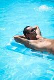 Homem novo que relaxa na piscina foto de stock