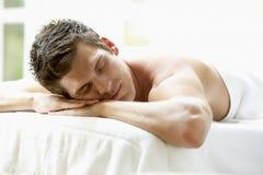Homem novo que relaxa na tabela da massagem Imagem de Stock Royalty Free
