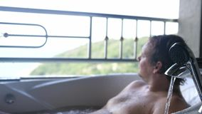 Homem novo que relaxa no Jacuzzi com opinião do mar na ilha tropical Movimento lento 3840x2160 vídeos de arquivo