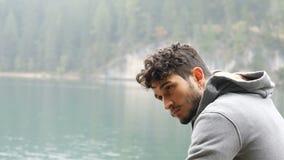 Homem novo que relaxa no lago da montanha video estoque