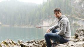 Homem novo que relaxa no lago da montanha vídeos de arquivo