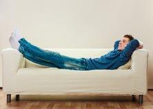 Homem novo que relaxa no sofá Fotos de Stock Royalty Free