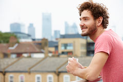 Homem novo que relaxa no terraço do telhado com xícara de café Fotografia de Stock