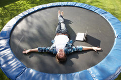 Homem novo que relaxa no Trampoline com portátil Fotos de Stock