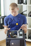 Homem novo que repara o computador Fotografia de Stock