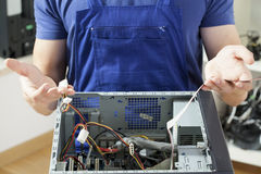 Homem novo que repara o computador Imagem de Stock