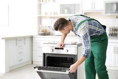 Homem novo que repara o forno foto de stock