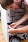 Homem novo que repara o refrigerador Imagens de Stock
