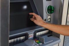 Homem novo que retira o dinheiro de uma máquina de dinheiro imagens de stock royalty free
