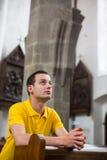 Homem novo que reza em uma igreja Imagem de Stock