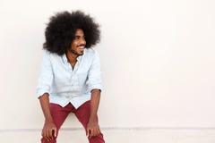 Homem novo que ri com mãos em joelhos e em afro fotografia de stock