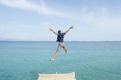 Homem novo que salta da doca no mar Foto de Stock Royalty Free