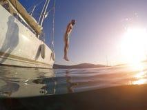 Homem novo que salta de um iate no mar Foto subaquática fotografia de stock