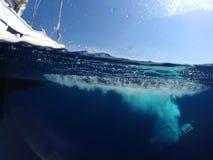 Homem novo que salta de um iate no mar Foto subaquática imagens de stock royalty free