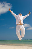 Homem novo que salta na praia Imagens de Stock