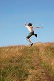 Homem novo que salta para a alegria fotos de stock royalty free