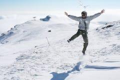 Homem novo que salta para o divertimento na neve Fotos de Stock Royalty Free