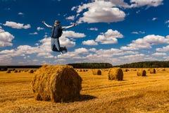 Homem novo que salta sobre o monte de feno no dia de verão foto de stock