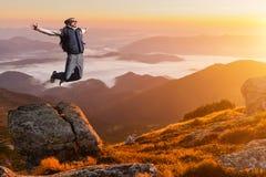 Homem novo que salta sobre uma montanha contra o céu imagem de stock