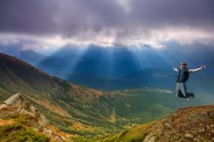 Homem novo que salta sobre uma montanha contra o céu imagens de stock royalty free