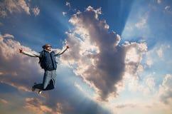Homem novo que salta sobre uma montanha contra o céu fotos de stock