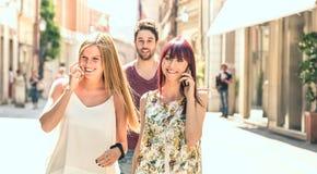 Homem novo que segue mulheres bonitas ao ter o divertimento junto na rua da cidade - conceito da tecnologia no estilo de vida diá imagem de stock