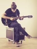 Homem novo que senta e que joga a guitarra Imagem de Stock